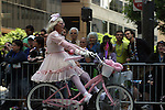 Gay man costumed as a small girl rides on bicycle at the Gay Pride parade