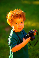 Portrait of a toddler boy with curly red hair and a shy smile, playing with a toy camera. Ben. Georgia.