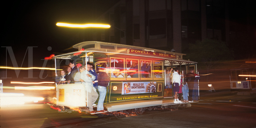 San Francisco, CA; Cable Car Full Of Passengers Crosses Intersection At Night