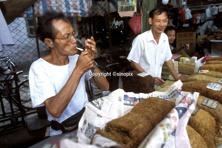 A tobacco vendor smokes a cigarette at a market in Guangzhou, China.
