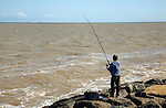 Man sea fishing  East Lane, Bawdsey, Suffolk, England