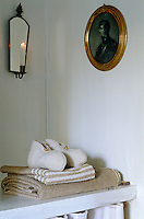 An antique mirrored candle sconce casts its gentle light above the dressing table in the bedroom