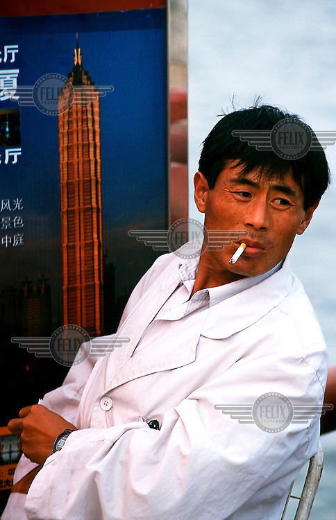 Mark Henley/Panos Pictures..China, Shanghai..Man smoking cigarette by image of the Jinmao Tower, tallest building in China, which lies across the Huangpu River from where he sits.