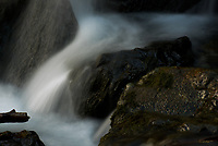 A small run of water catches sunlight as Pioneer Falls cascades down Pioneer Peak in Alaska's Chugacg Mountains.