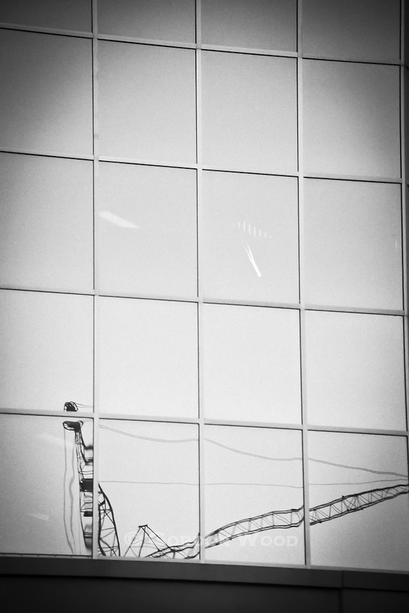 Reflection of Crane and Contrail  in Glass and Steel Office Building