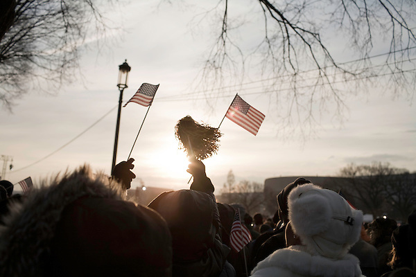 January 20, 2009. Washington, DC..Almost 2 million people packed the National Mall in sub freezing temperatures to witness the swearing in of Barack Obama, the 44th president of the united States and the first African American to hold the office. . A woman waves flags in an attempt to keep warm during the hours long wait for the speeches to begin.