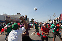 Los Angeles, CA -  Monday, June 23, 2014: Mexico fans kick a soccer ball around while celebrating Mexico's victory over Croatia on the streets of downtown Huntington Park.