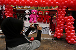 A Palestinian woman uses her mobile phone to take a photo for red teddy bears outside a shop on Valentine's day in Gaza city on February 14, 2017. Valentine's Day is increasingly popular in the region as people have taken up the custom of giving flowers, cards, chocolates and gifts to sweethearts to celebrate the occasion. Photo by Ashraf Amra