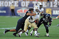 17 September 2011:  FIU defensive end Tourek Williams (97) loses his helmet while tackling UCF running back Brynn Harvey (34) in the second quarter as the FIU Golden Panthers defeated the University of Central Florida Golden Knights, 17-10, at FIU Stadium in Miami, Florida.