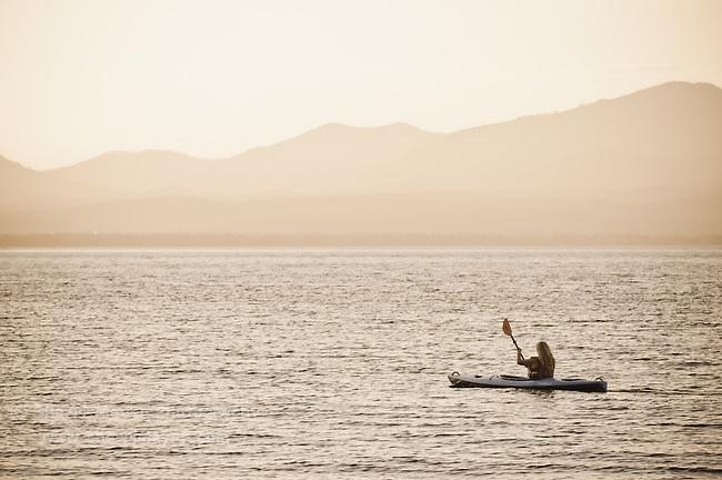 Woman kayaking at sunset on Lake Almanor, California.