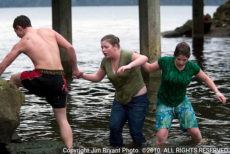 Sally Stuart (C) is helped out of the water by Elton Goodwin (L) and Susan Bell (R) after completing her first plunge in the 24th annual Polar Bear Jump into the Burley Lagoon in Olalla, Washington on January 1, 2008. Jim Bryant Photo. ©2010. ALL RIGHTS RESERVED.