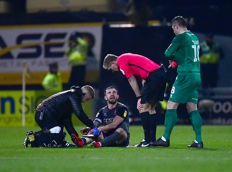 Lincoln City's Neal Eardley receives treatment from Lincoln City's head of sports science and medicine Mike Hine<br /> <br /> Photographer Andrew Vaughan/CameraSport<br /> <br /> The EFL Sky Bet League Two - Mansfield Town v Lincoln City - Monday 18th March 2019 - Field Mill - Mansfield<br /> <br /> World Copyright © 2019 CameraSport. All rights reserved. 43 Linden Ave. Countesthorpe. Leicester. England. LE8 5PG - Tel: +44 (0) 116 277 4147 - admin@camerasport.com - www.camerasport.com