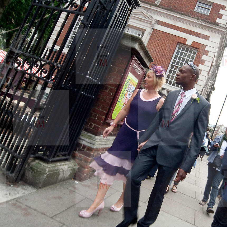 A couple of guests at a wedding walk down Piccadilly Street.
