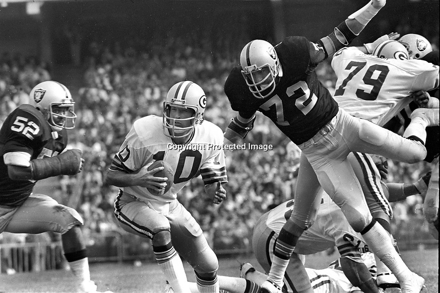 Oakland Raiders #72 John Matuszak , Green Bay QB Lynn Dickey, and Raider #52 Flord Rice. (1976 photo by Ron Riesterer)