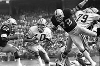Oakland Raiders #72 John Matuszak , Green Bay QB Lynn Dickey, and Raider #52 Flord Rice. (1976 photo by Ron Riesterer)
