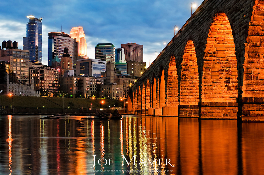 Minneapolis skyline and stone arch bridge at dusk with Mississippi River in foreground.