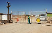 """Tor in der Roten Linie bei Palmwag: NAMIBIA, AFRIKA, 12.12.2019: Rote Linie.<br /> Der Zaun verläuft von der Küste im Westen nach Osten bis an die Grenze zu Botswana und entlang dieser. Er wurde kurz nach einem Ausbruch der Rinderpest im Jahr 1897 angedacht, Mitte der 1960er Jahre endgültig errichtet und besteht – in weiten Teilen – bis heute.<br /> Er soll eine unkontrollierte Bewegung von Fleisch, Vieh und tierischen Produkten von Norden nach Süden unterbinden. 1961, als es zu einem starken Ausbruch der Maul- und Klauenseuche im Norden Namibias kam, wurde der Zaun erneut verstärkt. Bis zum Ende der Apartheid mit der Unabhängigkeit Namibias im Jahr 1990, aber auch schon in der deutschen Kolonialzeit, hatte der Zaun jedoch eine weitere Funktion: Die im Norden Namibias lebenden Stämme konnten dadurch leichter vom ansonsten """"weißen"""" Namibia, der Polizeizone, ferngehalten werden. So kam diese """"rote Linie"""" den Südafrikanern bei der Durchsetzung ihrer Homeland-Politik sehr gelegen und bis 1977 durfte kein Ovambo diese Grenze ohne Genehmigung (z. B. in Form eines Arbeitsvertrages) überqueren."""