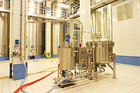 In the winery: a Filtrox kieselguhr (diatomite) filter in stainless steel in the main blending hall with big wine vats for fermentation or blending in the background, the Union Champagne cooperative, also called Champagne de Saint Gall in Avize, Cote des Blancs, Champagne, Marne, Ardennes, France