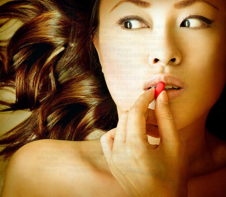 Close up of a young asian womans face placing a red pill to her lips
