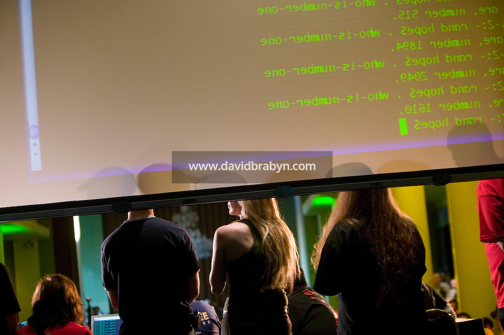 Organizers stand on stage below an overhead display during the closing events of the 6th edition of HOPE, an annual hackers' convention, listen to speakers, July 23rd 2006, New York City, USA.