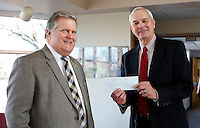 NWA Democrat-Gazette/DAVID GOTTSCHALK - 2/6/15 - Paul Hewitt (right), superintendent of Fayetteville Public Schools, accepts a check for $4,198 from Rusty Turner, editor of the Northwest Arkansas Democrat-Gazette, Friday February 6, 2015 at the Fayeteville Public School Administration Building in Fayetteville.