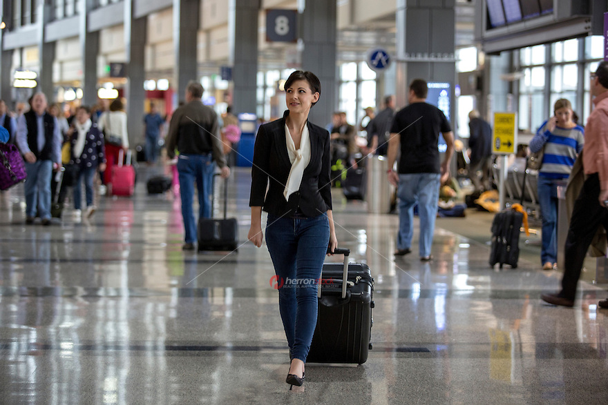 Young female traveler walks through the busy and crowded Austin–Bergstrom International Airport (ABIA) terminal, pulling suitcase luggage in hand.