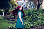 Young woman with long red hair wearing lace dress standing outdoors side on looking at camera