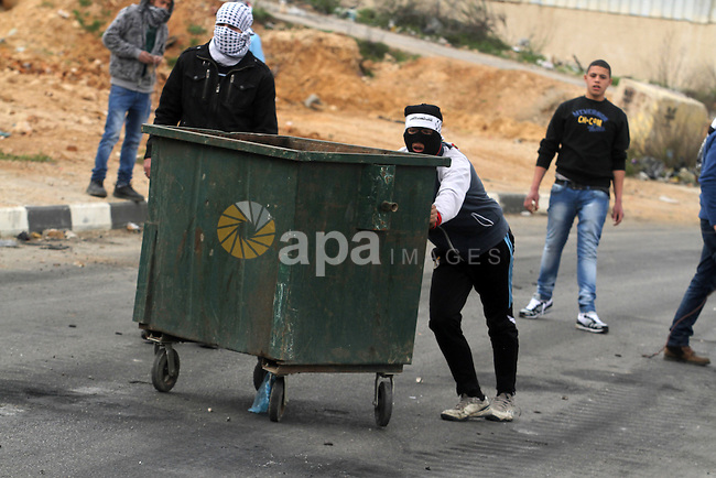 Palestinian protesters take cover during clashes next to the Israeli military prison 'Ofer' in Beitunya, south of Ramallah, the West Bank, 22 February 2013. Palestinian protesters clashed with Israeli security forces during a demonstration to show solidarity with Palestinian prisoners held by Israel. Photo by Issam Rimawi