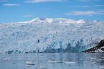 A group of intrepid zodiac explorers set against the face of a massive tidewater glacier at Cierva Cove, Antarctica