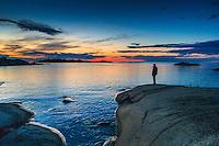 Man på en häll vid havet på Arholma i Roslagen Stockholms skärgård en sen kväll när solen har gått ned. / Man on a hob by the sea on Arholma in the Stockholm archipelago one late evening when the sun has gone down.