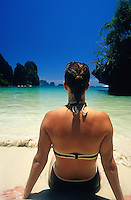 Woman in bikini relaxing on white sandy beach with turquoise water and blue sky, Phra Nang Beach, Railay Rei Lei, Thailand