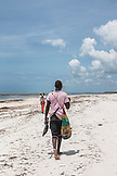 ZANZIBAR, Paje Beach, Two fishermen are walking on the beach after the tide holding their baskets