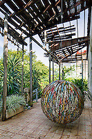 """The covered terrace reveals the condition of the house when Damian and Pamela acquired the property in 2008 and serves as another area to display one of Aquiles """"Infinite"""" objects"""