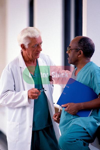 two doctors standing in hospital corridor discussing patient