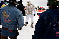 A man dressed as a yeti stands in the snow at the Whitefish Skijoring World Championship event in Whitefish, Montana, USA.  The yetis are a part of the White Winter Carnival.  Skijoring is a competitive sport in which a person on skis navigates an obstacle course while being pulled behind a galloping horse.