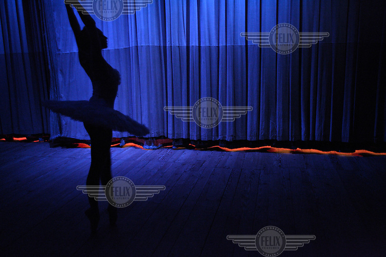 A ballerina from the Bolshoy ballet theatre company waits to perform on stage before the curtain is lifted at the Congress Hall in the Soviet-built Palace of Culture.