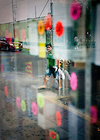 A woman is reflected in a store front window along Main Street in downtown McAllen, Texas, Sunday, April 4, 2010. Downtown McAllen stores don't sell designer or name brand items, but still reach a wide customer base for McAllen residents and visiting Mexican tourists. ...PHOTO/ Matt Nager