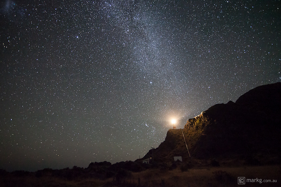 Cape Palliser Lighthouse on the south eastern tip of the North Island of New Zealand, lights up the surrounding landscape as the tail of the Milky Way extends skywards from behind.
