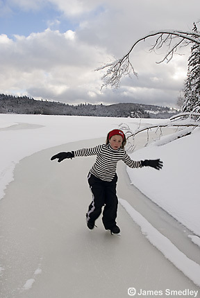 Family ice skating on a frozen lake during a northern ontario winter