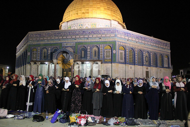 "Palestinian Muslim worshippers perform ""Taraweeh"", nightly prayer of the month of Ramadan, in front of the Dome of the Rock mosque, in Jerusalem's old city on June 21, 2016. Ramadan is sacred to Muslims because it is during that month that tradition says the Koran was revealed to the Prophet Mohammed. The fast is one of the five main religious obligations under Islam. More than 1.5 billion Muslims around the world will mark the month, during which believers abstain from eating, drinking, smoking and having sex from dawn until sunset. Photo by Mahfouz Abu Turk"