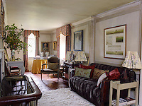 Warm terracotta tiles line the floor and the sofa is covered in a faux-fur throw in this intimate and cosy living room