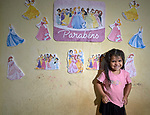Ana Rebecca, age 5, poses in front of film characters she has posted on the wall of a one-room apartment in a building in Manaus, Brazil. Her Kokama indigenous family migrated to the city in 2018, but unable to find decent housing they could afford, they joined with other poor families to take over an unoccupied building--the Casa do Estudante--in the city center. Caritas, a ministry of the Catholic Church, has helped the families in their struggle.<br /> <br /> Written parental consent obtained.