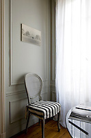 In the dining room an elegant cane-backed antique chair with a contemporary loose cover in black and white stripe is placed against the grey-painted wall panelling