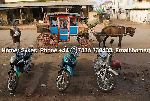 Pyin U Lwin. Myanmar (Maymeo Burma.) 2006. Three motorbikes and a traditional miniature stage coach being loaded up with market produce.