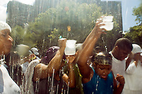 "Members of the United House of Prayer for All People, a non-denominational Pentecostal church in Harlem in New York on Sunday, August 3, 2008 collect water blessed by their bishop at a mass baptism. The church, which has held the baptisms on West 115 street since 1937, uses a fire hose to spray the congregation with city water blessed by the church's bishop. The ceremony is accompanied by music played by several brass ""shout"" bands. (© Frances M. Roberts)"