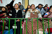 Women cheer whilst watching Cholitas wrestle at the Multifuncional building in El Alto. Cholitas are wrestlers of native Aymara descent and fight in traditional costume.