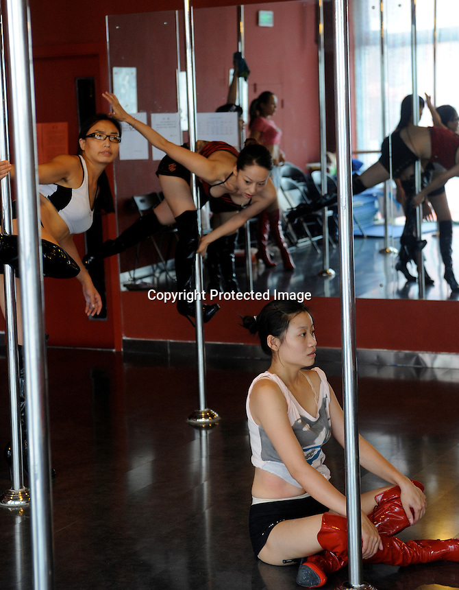"Dance studio in Beijing, China, 20 August 2008.  Students pay 20,000 RMB for 3 month courses i the hope of dancing in clubs in cities across the country and Beijing. Beijing which is currently hosting the Olympic Games has banned all kinds of entertainment, such as pole dancing, that says will taint it's image during the games but is widely expected to return to ""normal"" after the games.<br /> <br /> PHOTO BY RICHARD JONES"