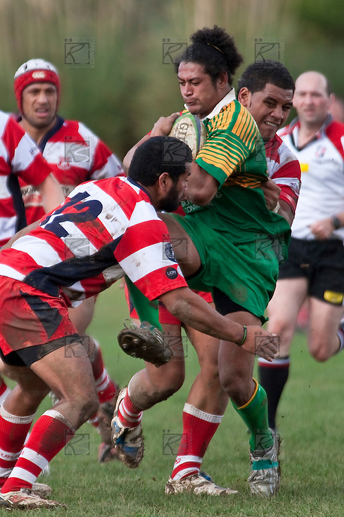 Visesio Finau charges into Cherethies Crichton and Siale Piutau. Counties Manukau Club rugby Premier game between Drury and Karaka played at Drury on Saturday May 1st, 2010. Karaka won the game 32 -12 after leading 25 - 7.