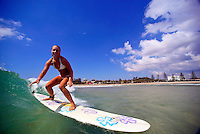 girl surfing a wave on a beautiful day in warm tropical water