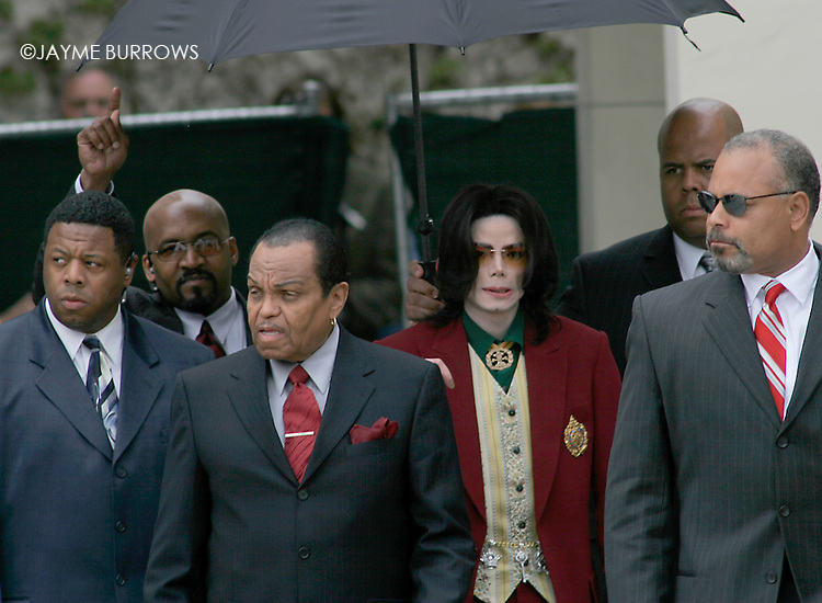 "Michael Jackson leaves the courtroom under heavy security after a man was removed from the fan area because he was making Jackson's security team ""nervous.""  This is the 14th day of Jackson's child molestation trial in Santa Maria, Calif on Thursday, March 17, 2005.  ...."